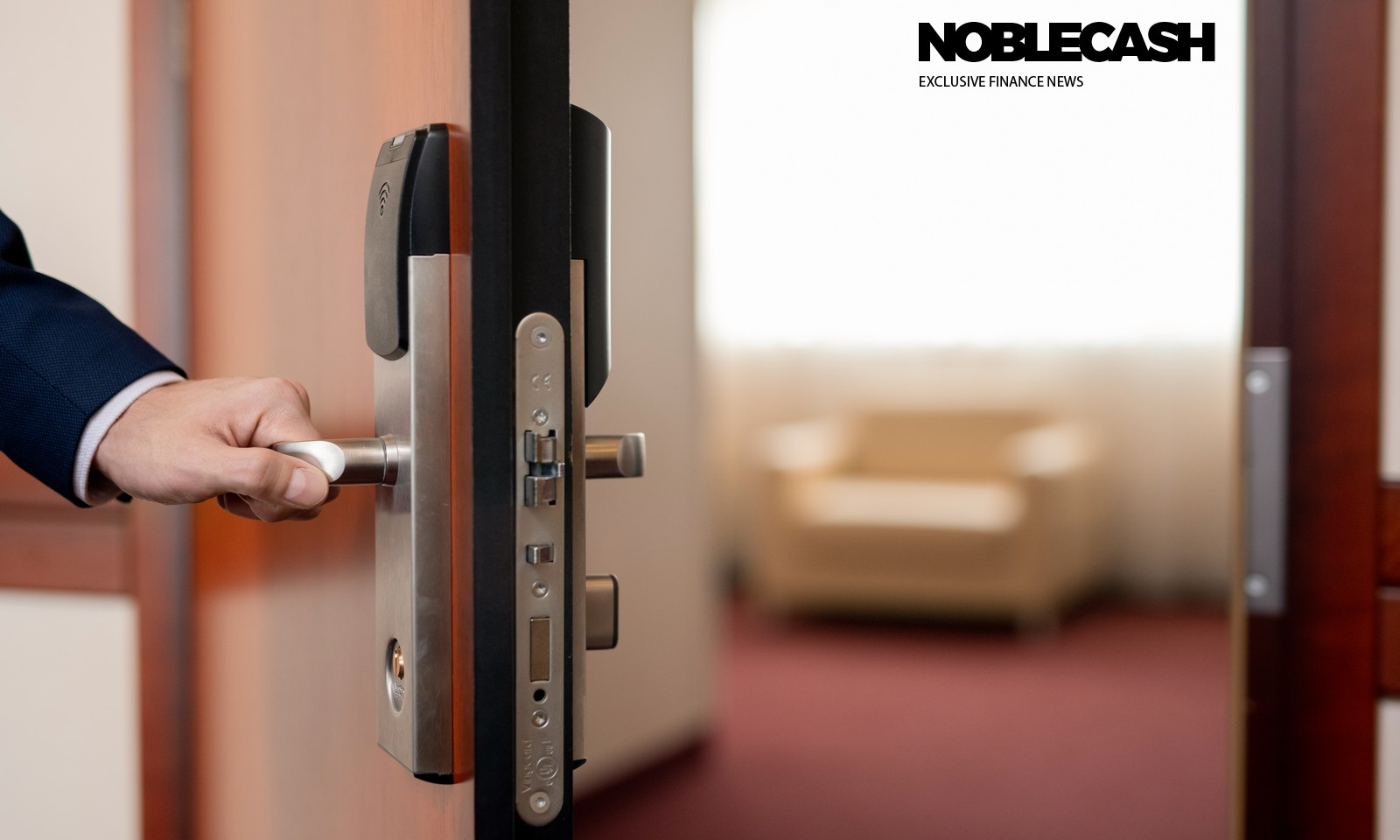 Human hand holding handle of wooden door while entering one of hotel room